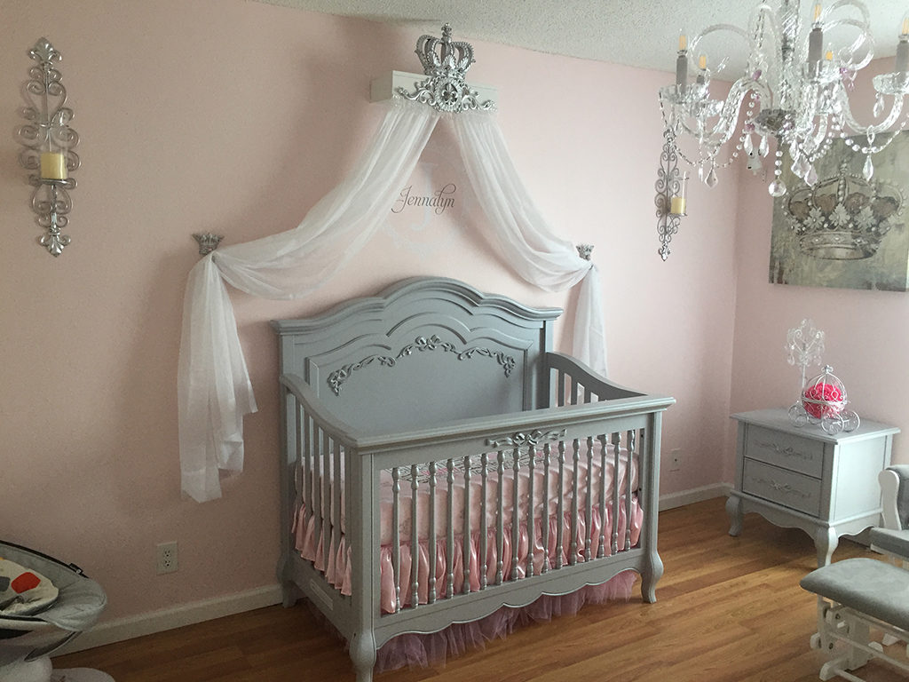 A crown canopy adds a touch of royalty to this gray and pink nursery